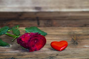 Róża i czerwone serduszko na drewnianym tle