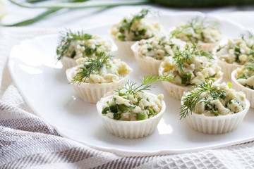 Tartlets with cheese and green onion filling decorated with dill on a dish