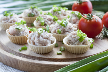 Tartlets with sowbelly  filling decorated with green onion on a wooden board