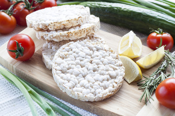 Plain rice cakes, galette rice with lemon, rosemary and vegetables on wooden board
