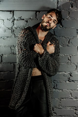 young trendy man with a beard, dressed in a fashionable jacket, at the bottom of a dungeon with brick walls and poor lighting. Paper black butterflies on the wall
