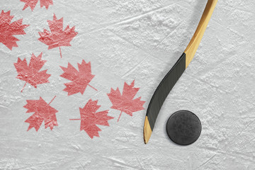 Hockey puck, hockey sticks and maple leaves