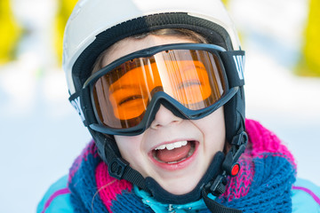 Ski, skier girl, winter vacation - happy child girl in goggles and protective helmet enjoining winter holidays