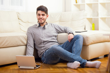 Man listening to music with earphones on laptop computer, sitting on the floor near the sofa