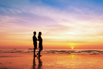 Couple sharing a romantic moment together on the beach, sunset
