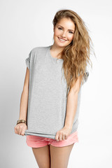 A blonde girl with beautiful curly hair into a blank gray T-shirt