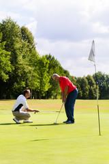 Senior man practicing golf with teacher helping