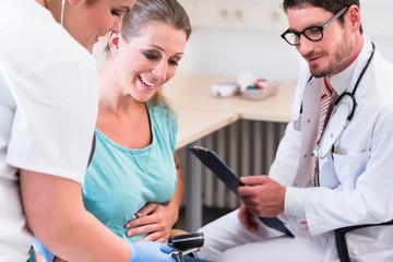 Arzt und Krankenschwester untersuchen schwangere Frau beim Frauenarzt