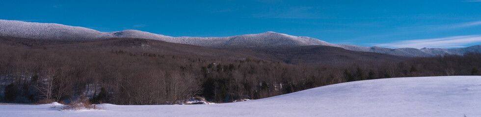 snow frosted mountians, tree covered hills and snowy fields making a Vermont winter landscape