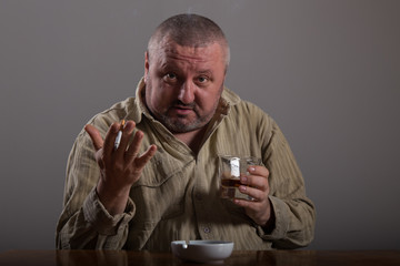 Alcoholism: portrait of a lonely, desperate man drinking alcohol and smoking cigarette