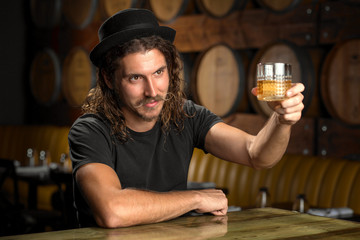 Whisky glass cheers stylish man drinking bourbon at a whiskey distillery restaurant bar
