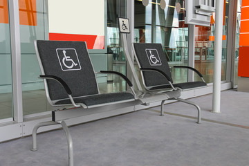 Two seats for people with disabilities in modern airport hall.