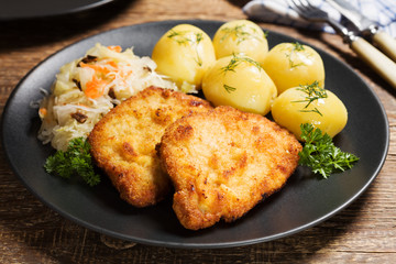 Fried pork chop in breadcrumbs, served with boiled potatoes and