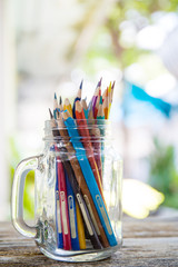 Glass jar containing colored pencils seen from above./Colored pe