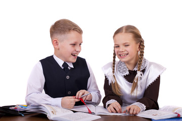 A couple of elementary school students sit at a desk