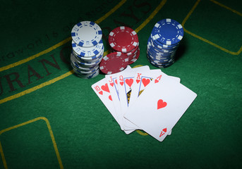 Cards and chips for poker on green table, top view.
