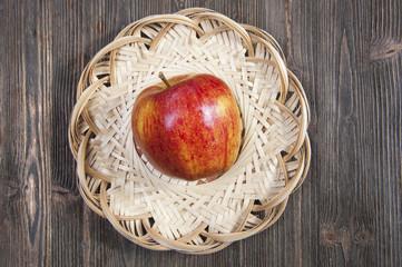 Яблоко в плетеной корзинке на деревянном фоне