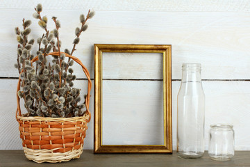 Golden wood photo frame with basket and bottle on wooden background