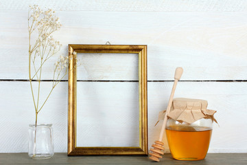 Golden wooden photo frame with a jar of fresh honey on wooden background