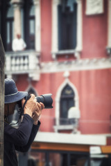 photographer records a snapshot on the background of Venetian ho