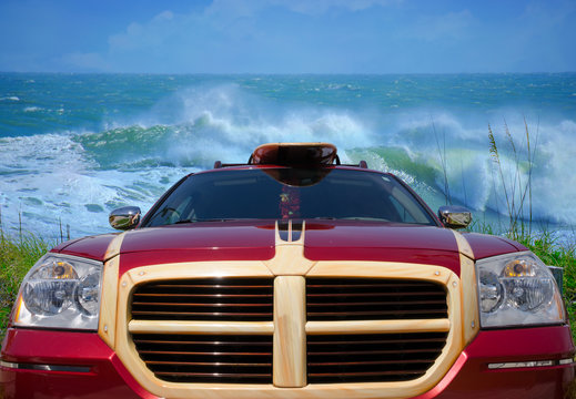 A red surfing car with surfboard racks and surfboard at beach with big huge wave in the background