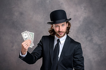 businessman with bowler hat in black suit showing money