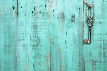 Bronze skeleton key hanging by rope on blank antique mint green rustic wood door