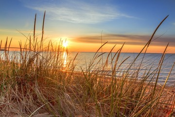 Dawn Of A New Day.Beautiful sunrise illuminates  sand dunes and the blue water horizon as a new day begins. Port Austin, Michigan.