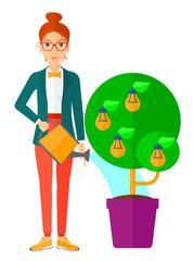 Woman watering tree with light bulbs.