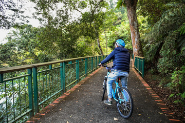 Young man cycling in the forest trail in cold weather during weekend