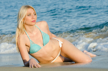 Blonde woman with amazing slim body wear bikini lying on the sand