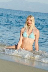 Blonde woman with amazing slim body wear bikini sitting in the sea, waves hitting her body