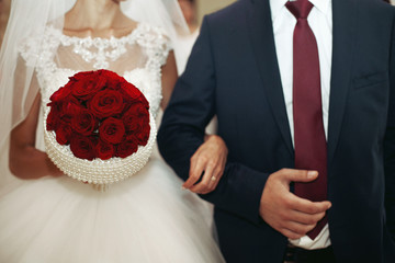 Closeup of newlywed couple holding hands and an elegant red rose