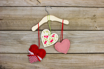 Red hearts and floral fabric heart hanging on hanger with wood background