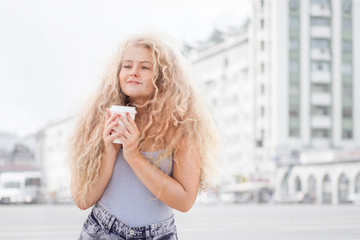 Happy smile / Happy smile. Happy young woman with long curly hair, holding a take away coffee cup and smiling against city background.