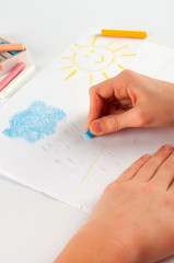 Child's hand, drawing a cloud.