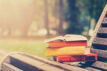 Stack of hardback books and Open book lying on bench at sunset park against blurred nature backdrop. Copy space, back to school. Education background. Toned image