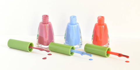 Three similar bottles of different nail polish on white background.