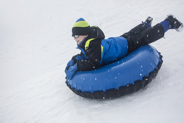 Child sledding down a hill on an inflatable snow tube