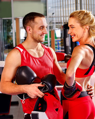 Female boxer with your male coach flirting in gym.