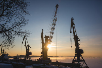 Silhouettes of cranes and industrial cargo ships in port at sunset or dusk, sea port with cranes and docks, in a sunny winter day, back light silhouettes
