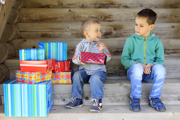 envious child. elder brother is jealous of a pile of gifts that are gifted to younger brother