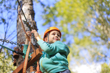 cheerful and brave boy at a height. child enjoys the view from the top in the ropes course and prepare for extreme downhill