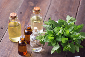 A lot of bottles with essential aroma oil with mint on wooden ba