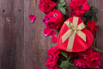 Red gift box in form of heart and red roses on aged wooden backg