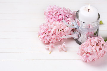 Background with white candle and fresh hyacinths flowers