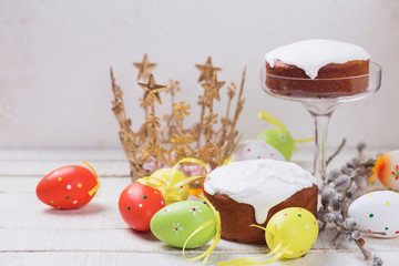Easter cakes, colorful easter eggs, willow branches on white woo