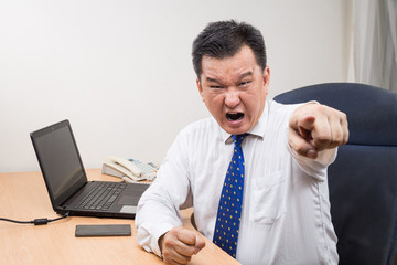 Angry and stressful Asian manager shouting and pointing in office