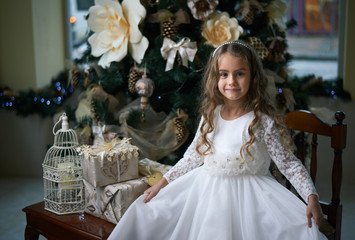 Playful girl sitting on  chair near the Christmas tree