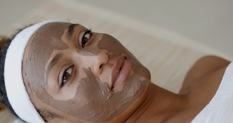Portrait of girl with a band on her head applying facial mask